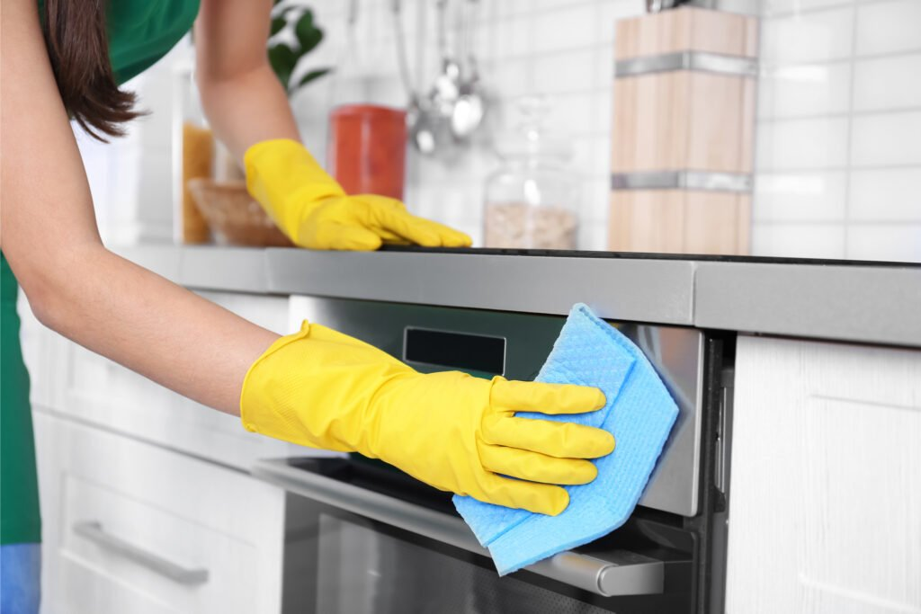 Woman with yellow rubber gloves wiping oven door, Martina's Cleaning, cleaner in Melksham and Devizes