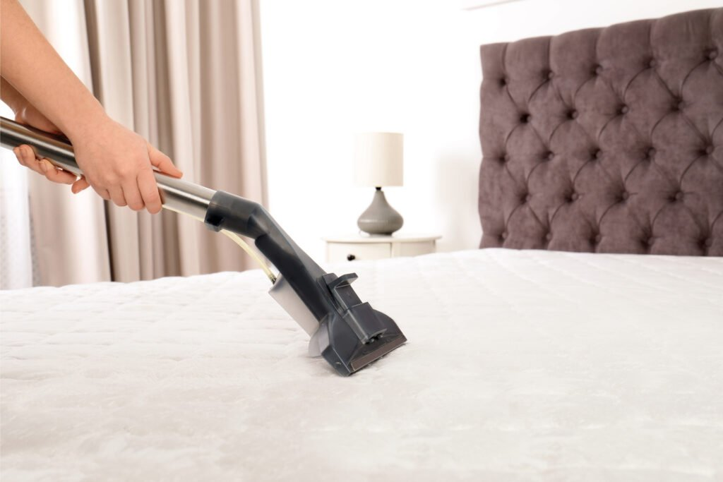 Hoovering mattress on bed, Martina's Cleaning, cleaner in Melksham and Devizes