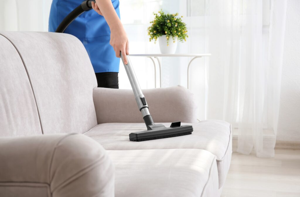 Woman hoovering sofa cushion, Martina's Cleaning, cleaner in Melksham and Devizes